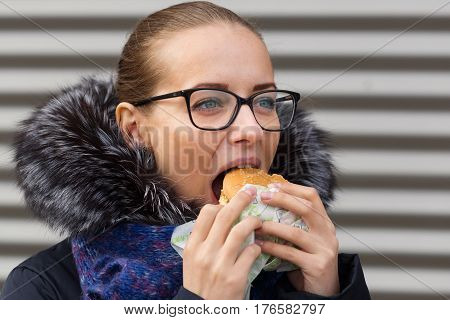 Beautiful Girl Eagerly Eats A Hamburger On The Street