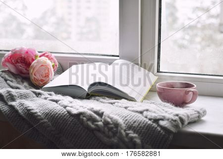 Cozy home still life: cup of hot coffee, spring flowers and opened book with warm plaid on windowsill. Springtime concept, free copy space.