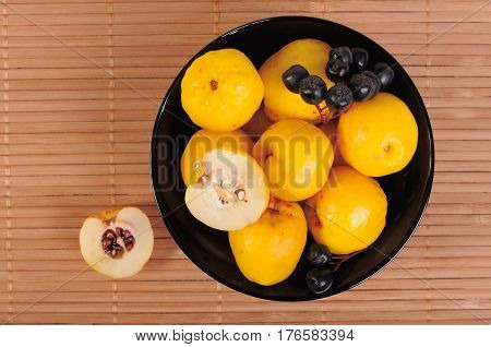 Quince with Black chokeberry in a bowl top view