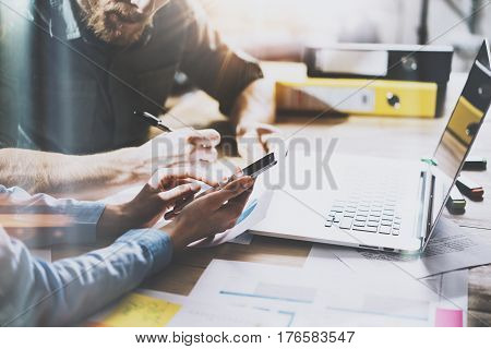 Teamwork process.Young coworkers work with new startup project in office.Analyze document, plans.Modern laptop on wood table, papers, documents.Horizontal, blurred, flare