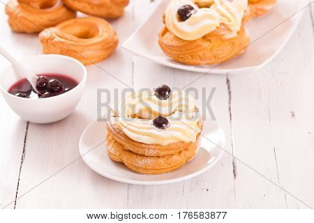 Zeppole with pastry cream and cherries in syrup.