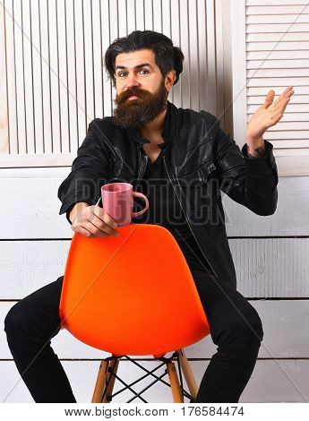 Bearded man long beard. Brutal smiling caucasian hipster with moustache holding cup or mug in rock black style sitting on acid orange chair on white wooden vintage studio background