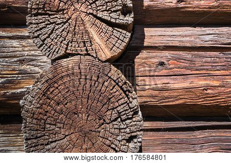 Wooden background. Close-up part of wall of old dilapidated longitudinal and transverse logs.