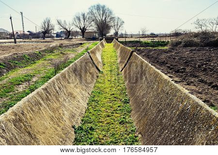 Dry irrigation canal on old farm field