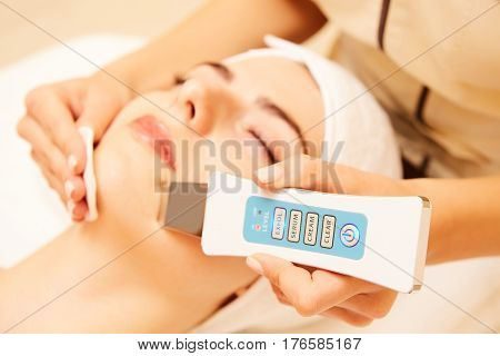 Doctor with Ultrasonic scraber. Doing procedure of ultrasonic cleaning of face. Model, profile. Cosmetological clinic. Patient. Healthcare, clinic, cosmetology