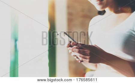 Happy smiling Asian woman holding mobile phone on hands and reading message at home room interior on the background. Flare effect. Selective focus on hands and smartphone.Crop