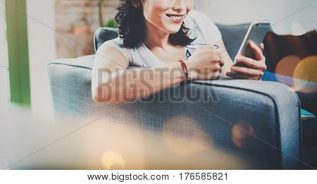 Young smiling Asian woman spending rest time at home on sofa, holding ceramic cup at hand and using smartphone for video conversation with friends.Blurred background, flares effect.Wide