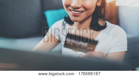 Happy attractive Asian woman using laptop and golden creditcard for online shopping while sitting on sofa at living room.Blurred background, flares effect. Wide