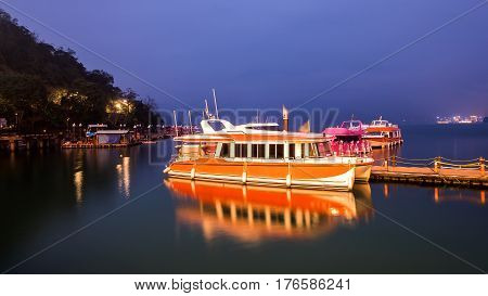 Long Exposure of harbor with boats in twilight time at Sun Moon Lake Nantou city Taiwan