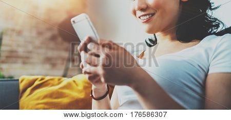 Closeup view of young smiling Asian woman sitting on sofa at home, wearing white tshirt and typing hands on smartphone.Horizontal blurred, flares effect.Wide.Selective focus