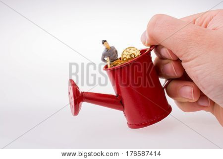 Figurine Standing In A Watering Can Full Of  Fake Gold Coins