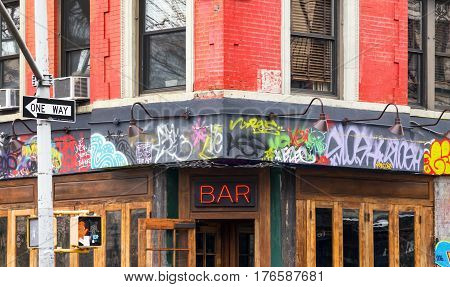 NEW YORK CITY - FEBRUARY 24: A local bar on the corner of Avenue A and St Marks is covered with graffiti in the East Village neighborhood of Manhattan in NYC on January 11th 2017.