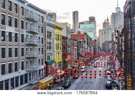 NEW YORK CITY - FEBRUARY 24: The colorful streets of Chinatown are crowed with stores restaurants signs cars and people with the downtown skyline of Manhattan in the background on February 24 2017.