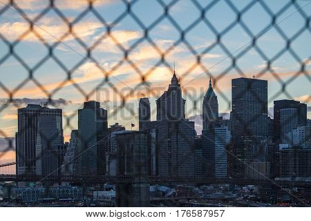 Colorful clouds of sunset behind New York City skyline seen through a fence on the Manhattan Bridge NYC