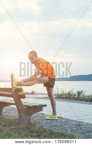 Young urban jogger stretching on the bench.