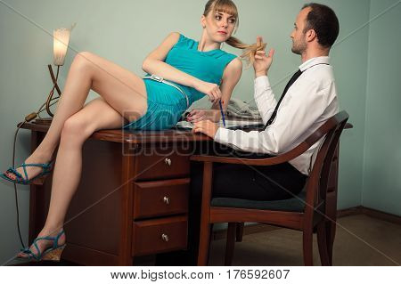 beautiful woman in blue dress lying on table in front the boss