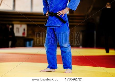 athlete judoka in blue kimono and black belt on tatami