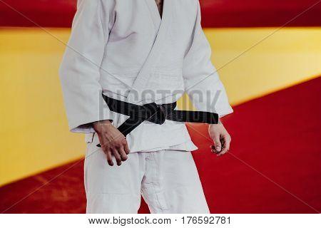 closeup man athlete judoka in white kimono and black belt