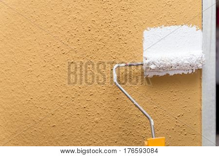 Paint Roller Painting A Brown Wall In White, Copyspace