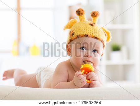 Funny baby boy in giraffe hat lying on his belly in nursery. Little kid infant using nibbler.