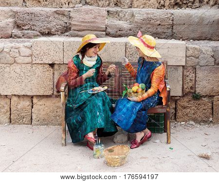 Participants Of Festival Dressed As Artist On Bench And Paint