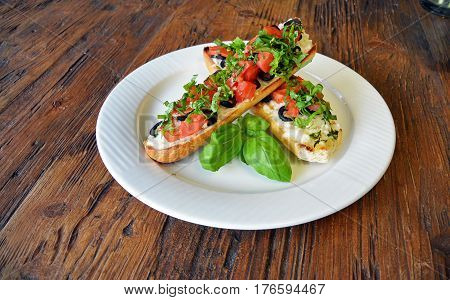 Preparing delicious Italian tomato bruschetta with chopped vegetables, olives, cheese and oil on grilled or toasted crusty baguette sprinkled with seasoning and spices on a plate on wooden background
