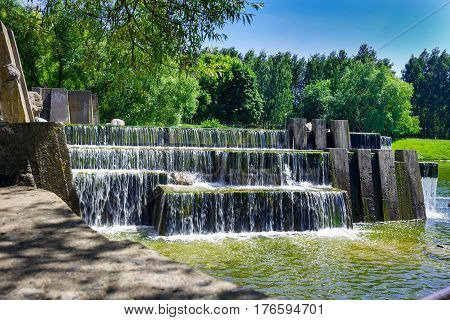 Summer landscape with a waterfall. A small waterfall in a public park