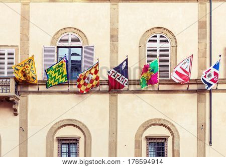 Siena medieval building decorated with district flags during traditional Palio horse race