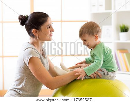Happy mother with baby son doing gymnastics on the big fitness ball in the gym
