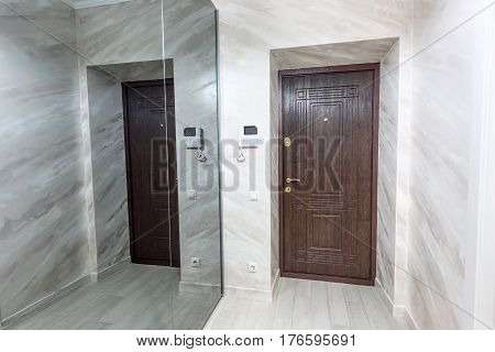 Stock photo white apartment interior hall design with brown entrance door and mirror wall, modern style, chisinau, moldova