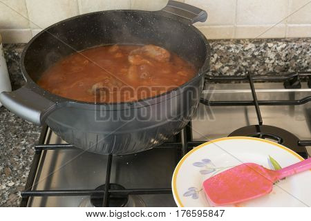 cooking beef goulash with sausages and tomato sauce
