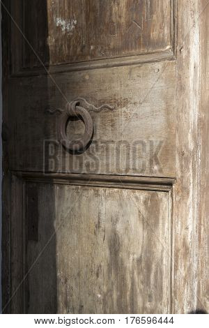 detail of an old wooden doorway with rusted knocker