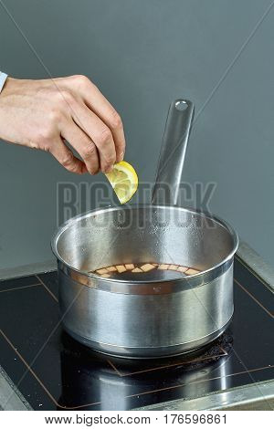 The cook sips the ingredients in a pan for cooking mulled wine culinary recipes