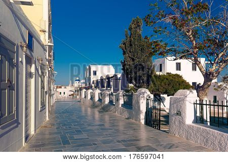 Central tourist street of Oia or Ia with white houses and church with blue domes, island Santorini, Greece
