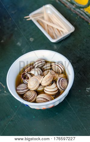 Isolated boiled or cooked snails with striped shells in smaall bowl with toothpicks on table, Marrakesh, Morocco.