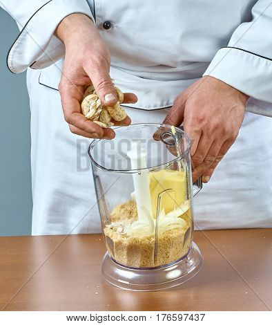 The cook puts in the blender ingredients for cooking stuffed fish collection of culinary recipes