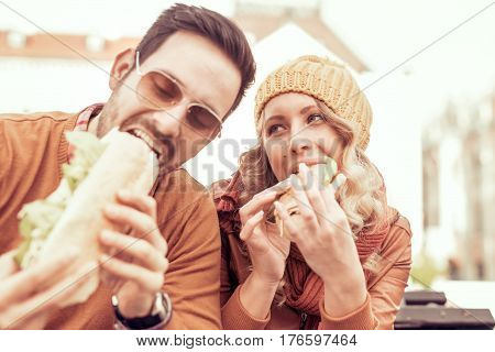 Young couple eating sandwich outdoors, close up