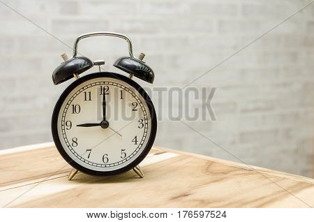 retro vintage alarm clock on wooden table with wall background, retro vintage concept with copy space for text.