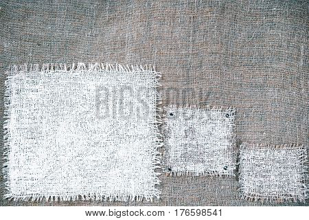 Rectangle pieces of white burlap pinned as various frames on gray burlap background. Rustic style eco-friendly universal template