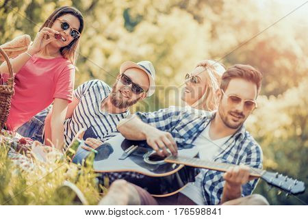 Happy young friends having picnic in the park. They are all happy having fun smiling and playing guitar.