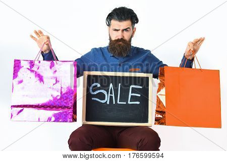 Bearded man long beard. Brutal caucasian squinting hipster with moustache holding pink and orange shopping packages and sale inscription on blackboard sitting on chair isolated on white background
