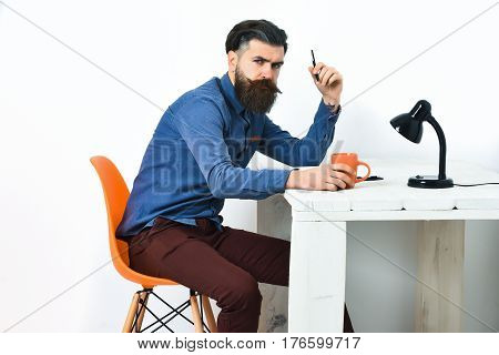 Bearded man long beard. Brutal caucasian unshaven serious hipster with moustache holding black pen at white vintage wooden table with open notepad black lamp and orange mug on it isolated on white