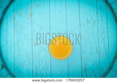 Glass of orange juice on blue vintage table. Flat lay. Shallow DOF