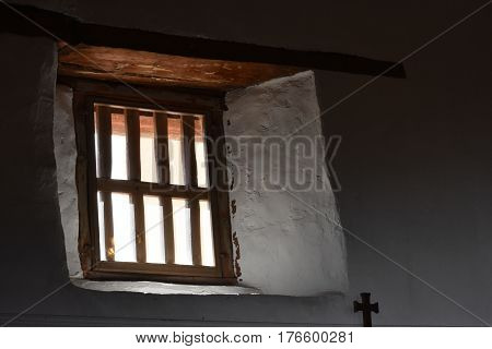 Adobe walls and a wooden window in a catholic church