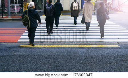 business and worker people walk on pedestrian crosswalk at the junction street of city with the white and yellow symbol signage traffic (bottom view)