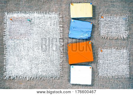 Rectangle pieces of white burlap and colorful wood pinned as various frames on gray burlap background. Rustic style eco-friendly universal template