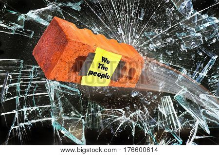 We the People brick through glass wall.