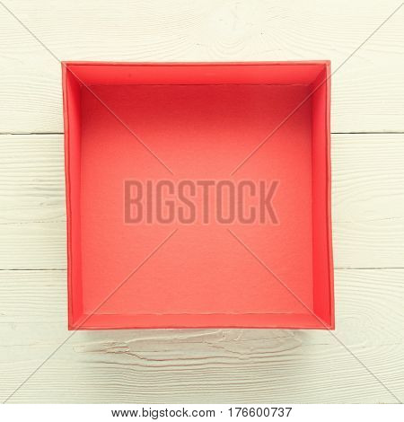 Close-up of empty red box on white wooden background. Flat lay. Top view with copy space