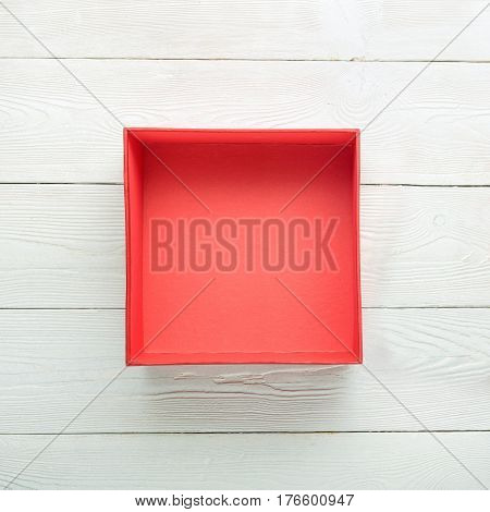 Open red gift box on white wooden background. Flat lay