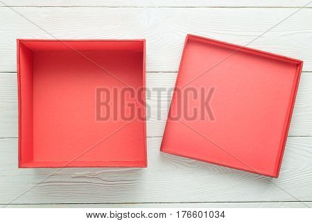 Empty gift box with lid on white wooden background. Flat lay